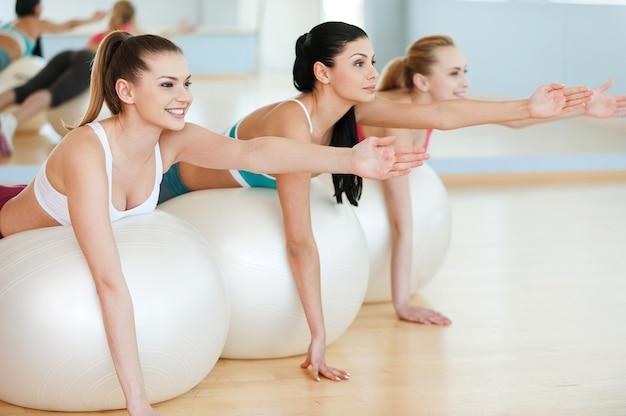 Entraînement avec des ballons de fitness. trois belles jeunes femmes en vêtements de sport