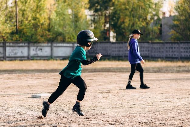 Entraînement de baseball, garçon après la course à la position de départ