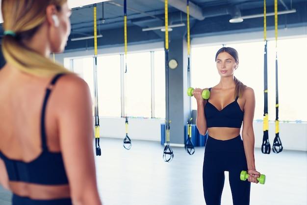 Entraînement de belle femme avec des haltères devant le miroir, salle de gym.