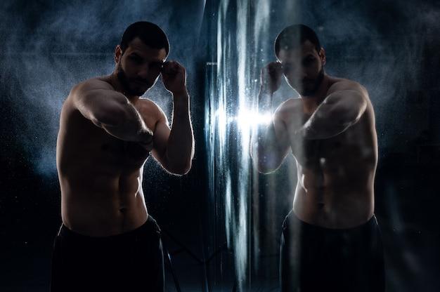 Entraînement de boxeur dans la salle de gym avec reflet en photo discrète pour la publicité du club de combat. photo de haute qualité
