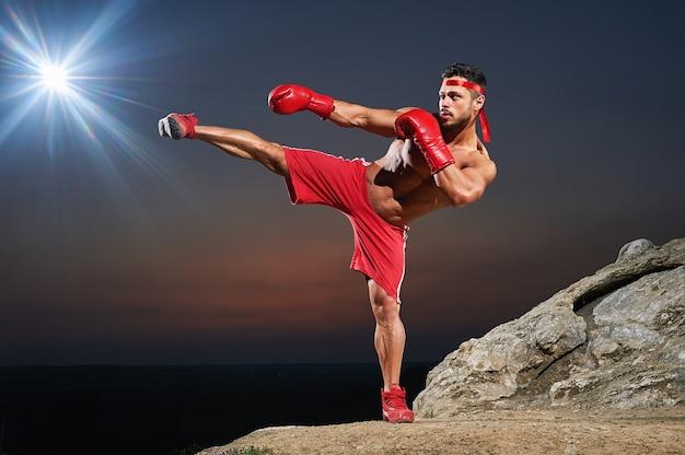 Entraînement de boxeur masculin musclé à l'extérieur