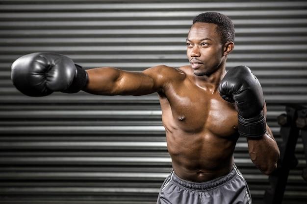 Entraînement de boxeur sans chemise au gymnase de crossfit