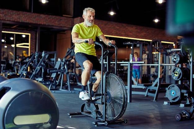 Entraînement cardio sur toute la longueur d'un homme athlétique mature en vêtements de sport faisant du vélo sur des vélos d'exercice