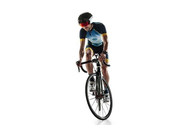 Entraînement de cycle d'athlète masculin de triathlon isolé sur fond de studio blanc. triathlète en forme de race blanche pratiquant le cyclisme portant des équipements de sport. concept de mode de vie sain, sport, action, mouvement.