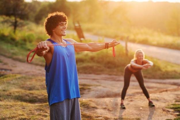 Entraînement dans la nature par une journée d'été ensoleillée. formation de couple sportif concentré heureux ensemble.