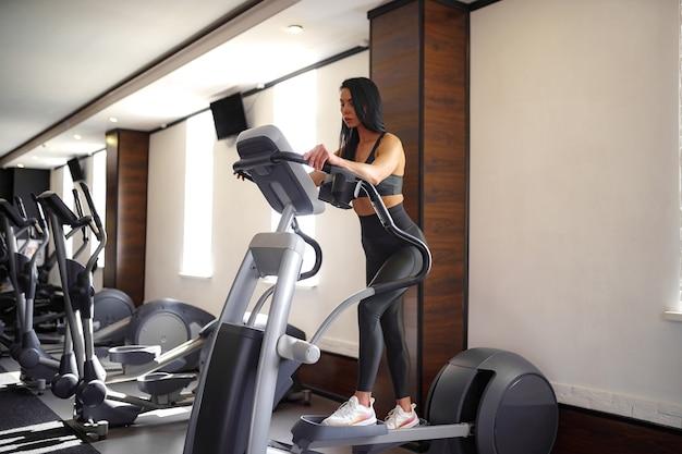 Entraînement dans la salle de gym fitness girl coach travaillant sur step machine et montrant sa silhouette posant dans un costume de sport