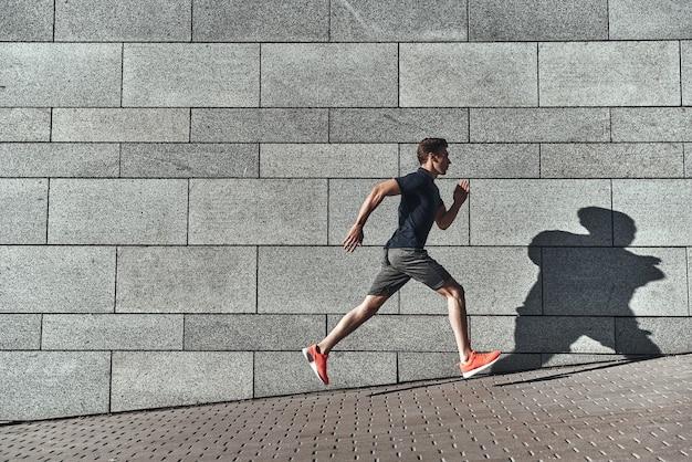 Entraînement du matin. toute la longueur du jeune homme en vêtements de sport courant tout en faisant de l'exercice à l'extérieur