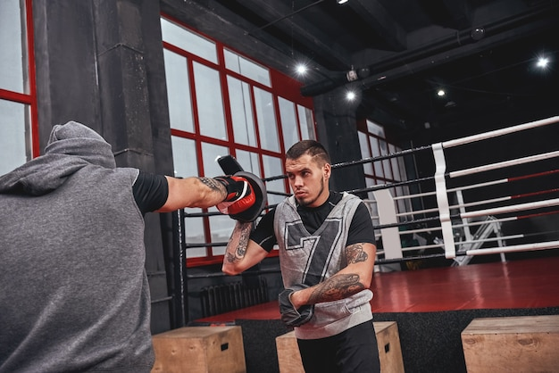 Entraînement dur. athlète tatoué musculaire confiant dans des gants rouges frappant aux pattes de boxe avec son partenaire sur fond de salle de sport coloré