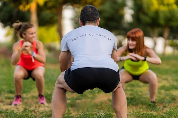 Entraînement d'entraîneur de fitness masculin dans le parc avec deux femmes heureuses et faisant des squats.