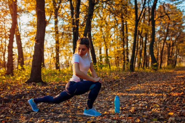 Entraînement et exercice dans un parc en automne. jeune femme qui s'étend de jambes à l'extérieur. mode de vie sain et actif