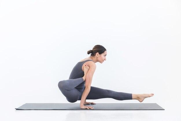Entraînement d'extension du corps. femme flexible yogi pratique le yoga sur tapis en studio