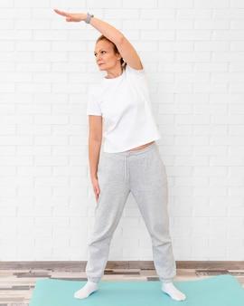 Entraînement de femme plein coup sur tapis de yoga