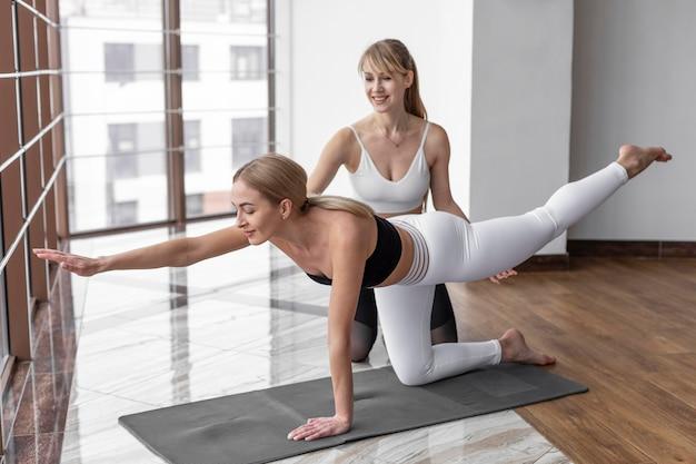 Entraînement de femme plein coup avec tapis de yoga