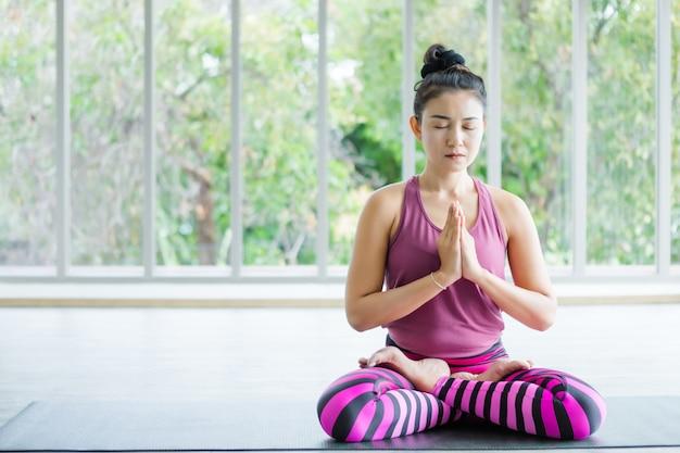Entraînement des femmes asiatiques pratiquant la formation de yoga mettre des vêtements roses et pratiquer la méditation bien-être et le concept de remise en forme de santé dans un gymnase