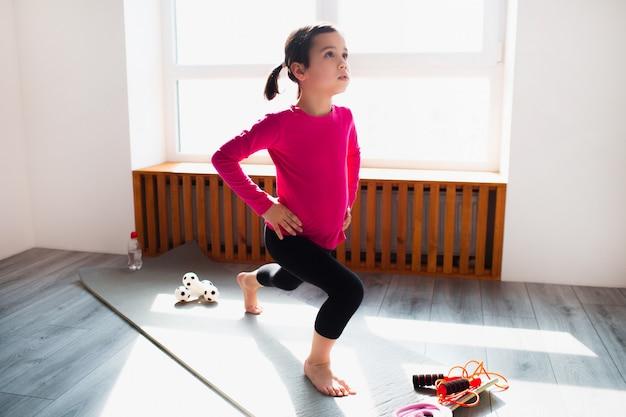 Entraînement de fente avant de petite fille à la maison. un enfant mignon s'entraîne sur un tapis à l'intérieur.
