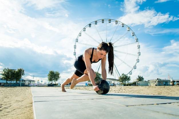 Entraînement fonctionnel sur la plage, femme en forme et athlétique faisant du sport en plein air