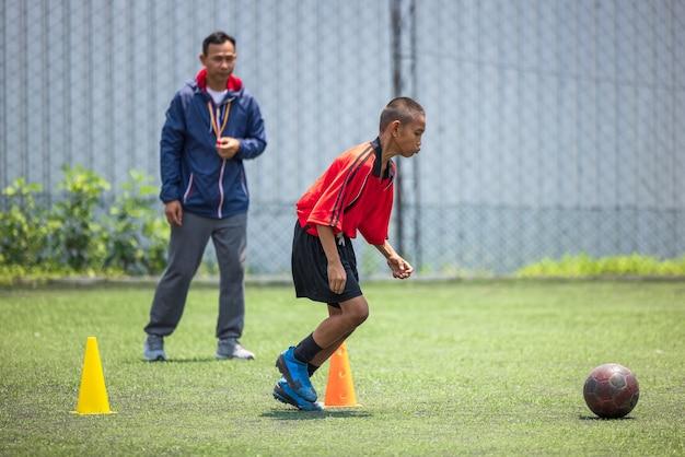 Entraînement de football de football pour les enfants. entraîneur expliquant le plan de match. jeunes garçons améliorant leurs compétences de football local en thaïlande