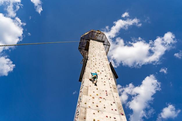 Entraînement de grimpeur sportif en plein air avec ciel bleu, escalade sur une paroi rocheuse colorée artificielle