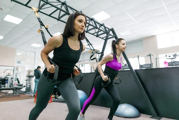 Entraînement en groupe avec des boucles de fitness dans le gymnase