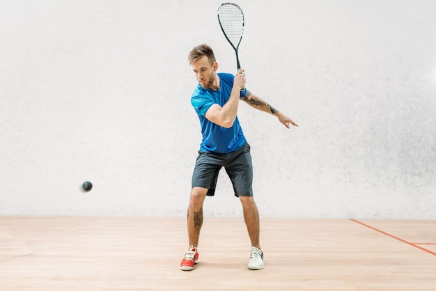 Entraînement de jeu de squash, joueur masculin avec raquette et balle