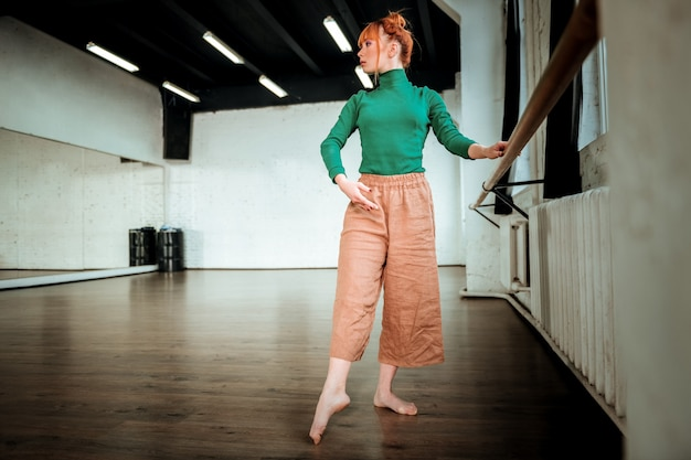 Entraînement. jeune danseuse moderne professionnelle aux cheveux rouges portant un col roulé vert travaillant pas