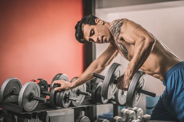 Entraînement. jeune homme avec un tatouage sur une poitrine travaillant dur dans une salle de sport