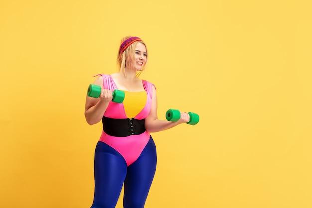Entraînement d'un jeune modèle féminin de taille plus caucasienne sur un mur jaune. espace de copie. concept de sport, mode de vie sain, corps positif, mode, style. femme élégante pratiquant avec des poids verts.