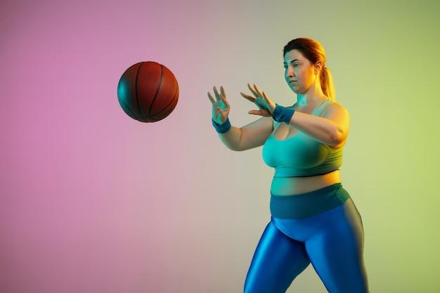 Entraînement d'un jeune modèle féminin de taille plus caucasienne sur un mur vert violet dégradé