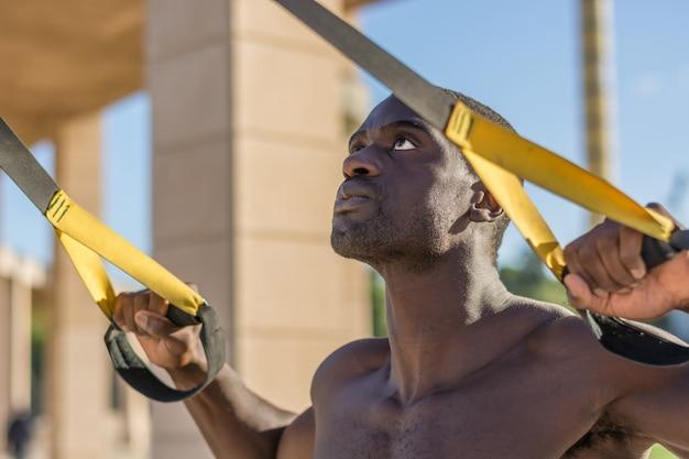 Entraînement musculaire masculin avec le système trx