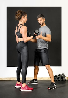 Entraînement personnel aidant une femme avec des poids