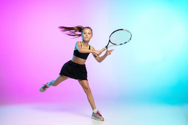 Entraînement. petite fille de tennis en tenue de sport noire isolée sur dégradé
