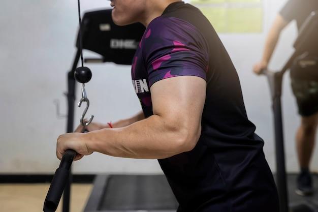 Un entraînement pour homme avec câble triceps pushdown au gymnase.