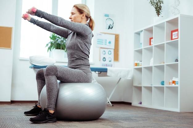 Entraînement de remise en forme. belle belle femme assise sur le ballon médical tout en ayant une séance d'entraînement de remise en forme