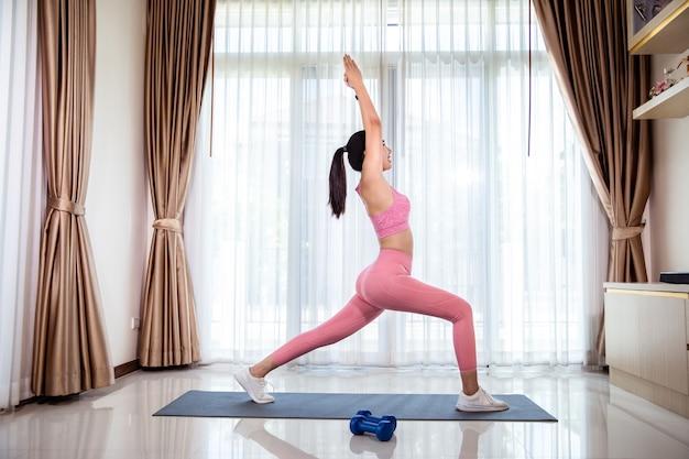 Entraînement de remise en forme de la femme asiatique à la maison. elle apprend de nouveaux exercices en regardant des tutoriels d'entraînement en ligne sur elle à la maison.