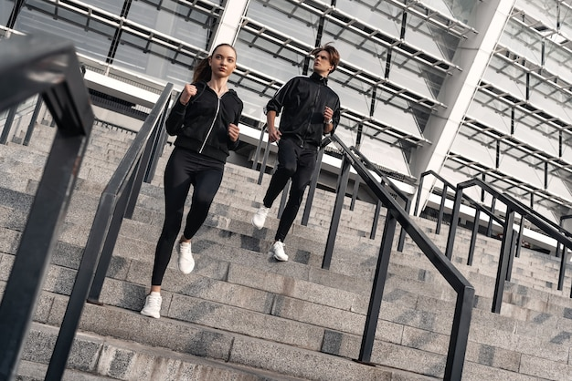Entraînement tôt le matin. jeune couple courant en bas près du stade de football. vivre un mode de vie sain.