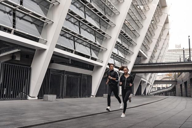 Entraînement tôt le matin. jeune couple courant près du stade de football. vivre un mode de vie sain.