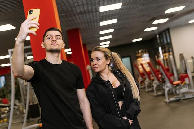 Entraînements personnels avec un entraîneur. un entraîneur physique et une femme prennent un selfie dans la salle de sport.