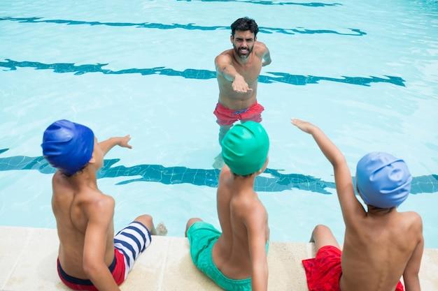 Entraîneur et étudiants prêtant serment dans la piscine du centre de loisirs
