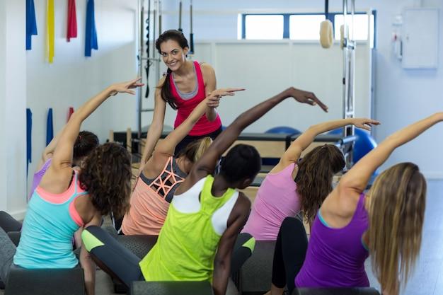 Entraîneur féminin aidant un groupe de femmes avec des exercices d'étirement sur arc baril