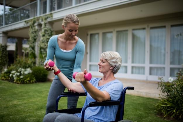 Entraîneur féminin aidant senior woman dans l'exécution de l'exercice