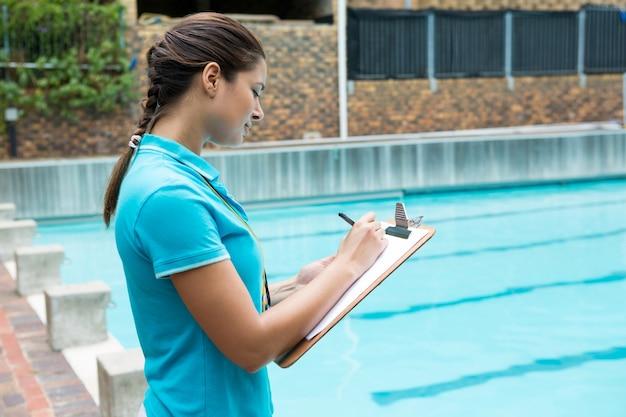 Entraîneur féminin écrit sur le presse-papiers près de la piscine