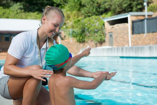 Entraîneur féminin entraînant un garçon pour la natation