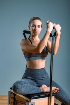 Entraîneur féminin posant pour un réformateur dans la salle de gym