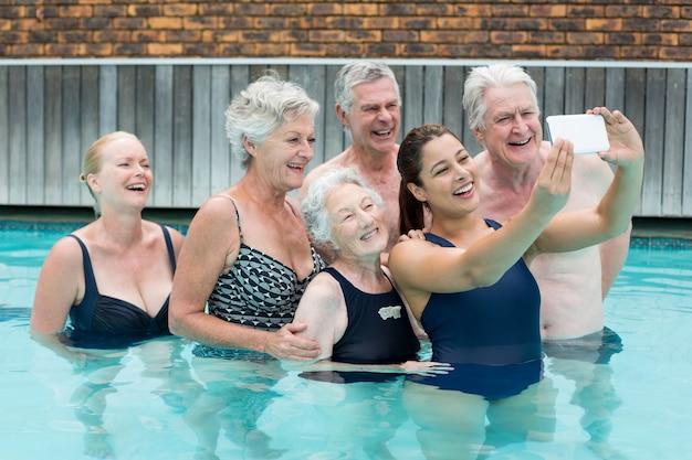 Entraîneur féminin prenant selfie avec des nageurs seniors dans la piscine
