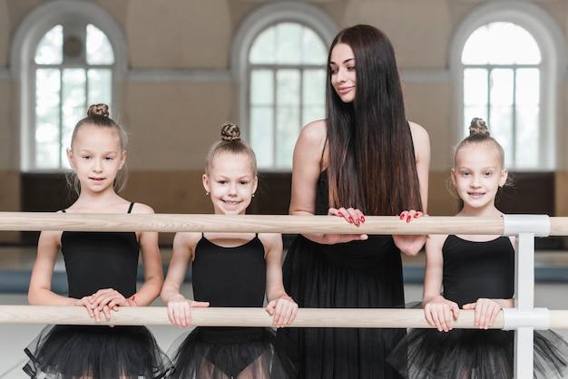 Entraîneur féminin regardant trois ballerines debout derrière la barre