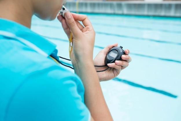 Entraîneur féminin sifflet et regardant chronomètre près de la piscine