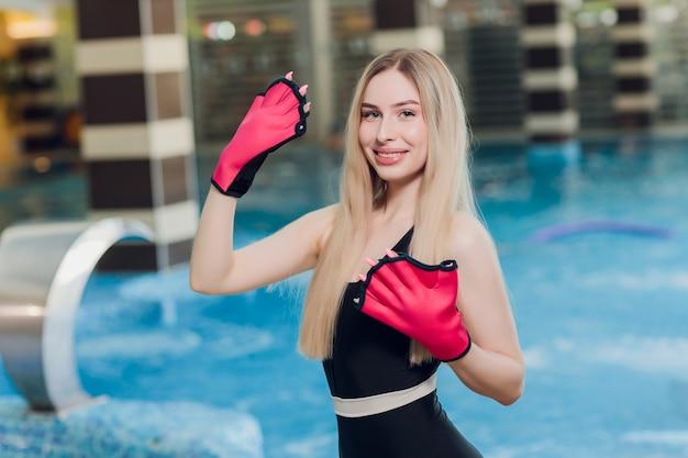 Entraîneur femme avec des gants dans l'eau de la piscine pour enfants et adultes