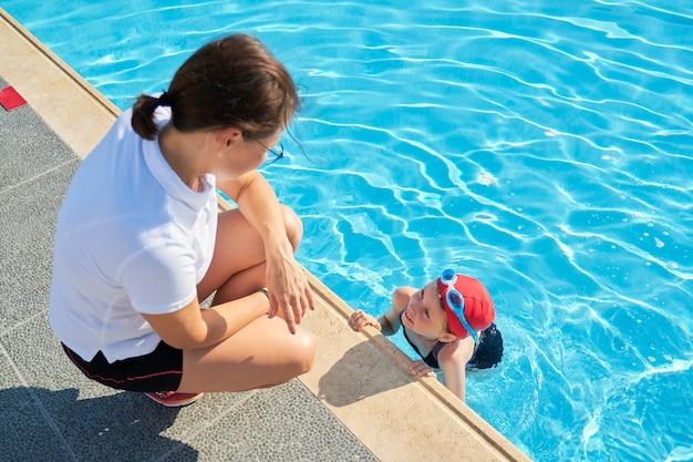 Entraîneur de femme parlant à la petite fille en chapeau de maillot de bain et lunettes près de la piscine extérieure