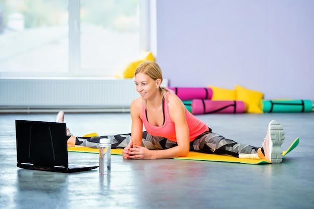 Entraîneur de femme sportive mène seul l'entraînement en ligne devant un ordinateur portable dans une salle de sport