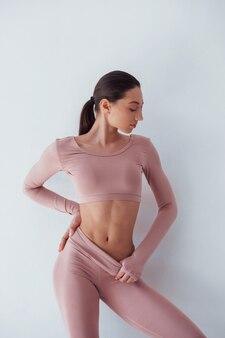 Entraîneur de fitness féminin. caucasienne jolie femme se dresse sur fond blanc